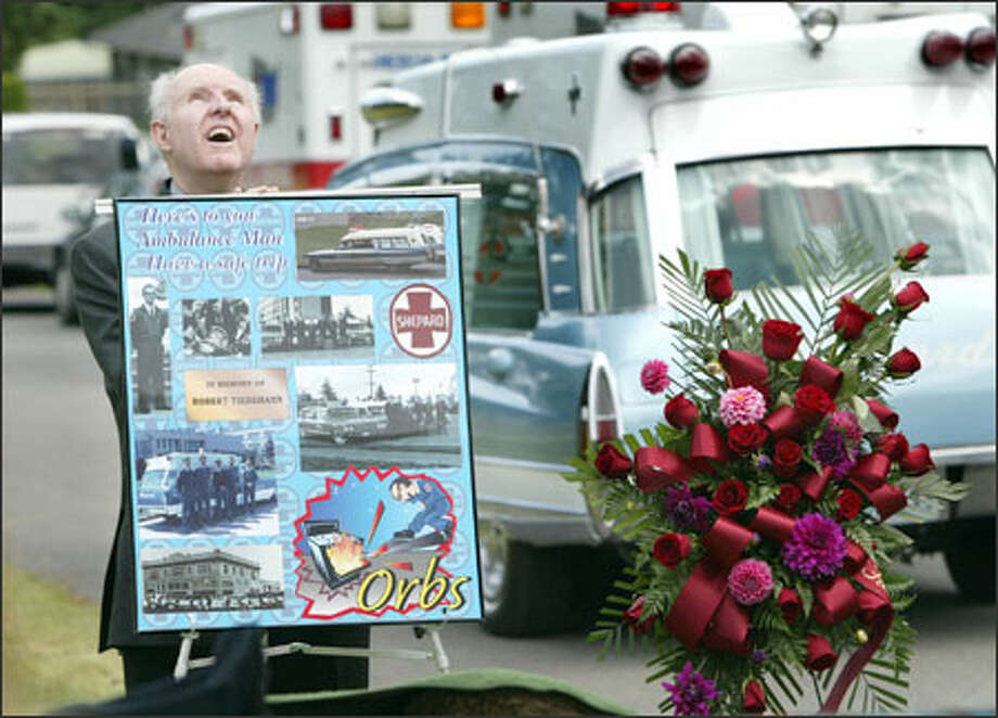 "Former co-worker Robert McRae looks skyward as others share stories during a memorial service for Robert W. ""Orbs"" Tiedemann, a longtime ambulance driver for Shepard Ambulance known for his quirky ways. Tiedemann, 64, who had no family, died last month of congestive heart failure and was to be buried in a communal plot, until friends and former co-workers stepped in and organized a service and funeral for him at Hillcrest Burial Park in Kent. The ambulance in the background carried Tiedemann's casket. Photo: Scott Eklund, Seattle Post-Intelligencer / Seattle Post-Intelligencer"