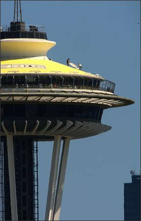 Workers apply yellow paint and logos atop the Space Needle, which will make the top resemble a record, in preparation for the Seattle-based record label Sub Pop's 20th anniversary. Famous bands launched by the label include Nirvana, Soundgarden and Mudhoney. Nearly two dozen bands from Sub Pop's past and present will perform this weekend. Photo: Dan DeLong, Seattle Post-Intelligencer / Seattle Post-Intelligencer