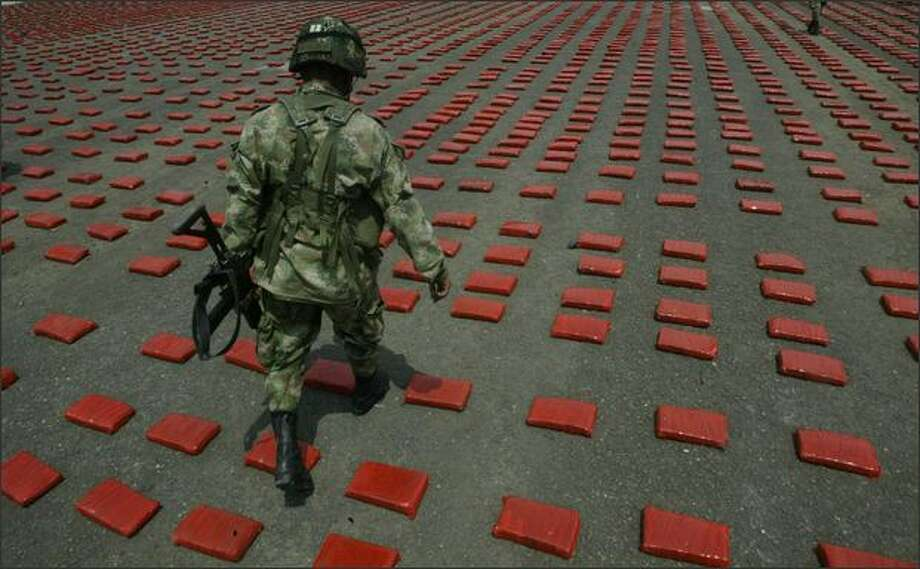 A soldier walks among packs of seized marijuana at a military base in Cali, Colombia. (AP Photo/Christian Escobar Mora) Photo: Getty Images / Getty Images