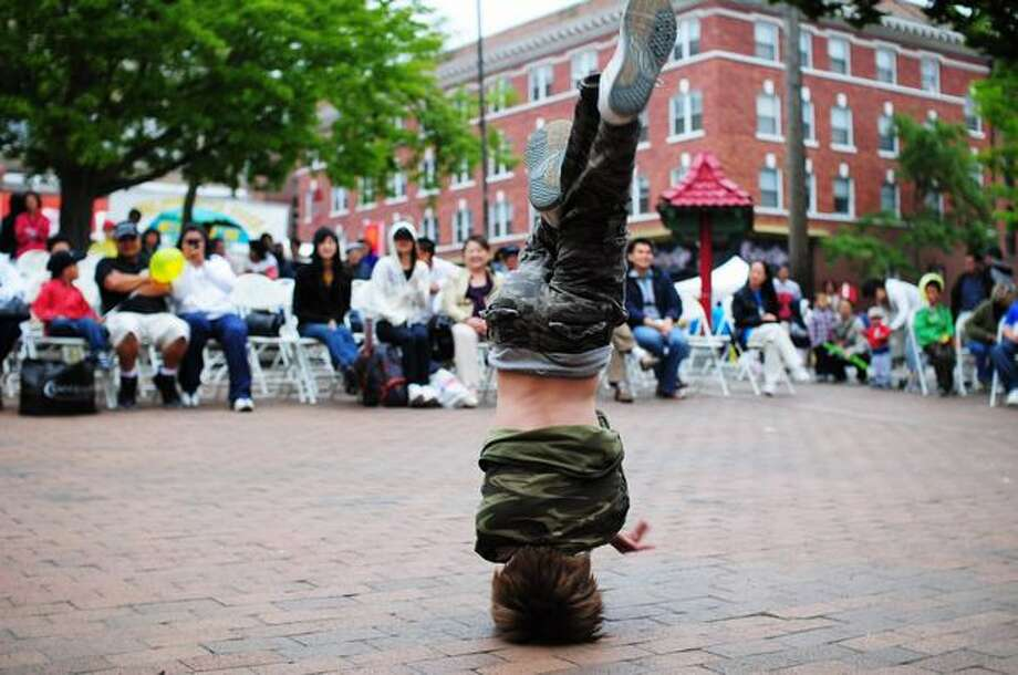 Daniel Wilsty spins on his head while dancing as guitarist Angelo Pizarro performs during the International District Summer Festival at Seattle's Hing Hay Park Saturday. Photo: Daniel Berman, Seattlepi.com / Seattlepi.com