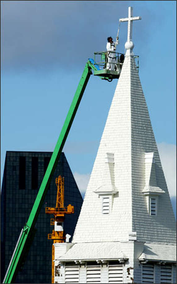 The historic Immanuel Lutheran Church, founded in 1890, is being painted for the first time in 25 years. Contractors estimate the job at 1215 Thomas St. in Seattle will take 30 days. The painters began at the top, with Mel Bradford and Richard Turner painting the steeple. The steeple's top is 130 feet above ground. The church was originally built to serve the city's Norwegian population. Photo: Paul Joseph Brown, Seattle Post-Intelligencer / Seattle Post-Intelligencer