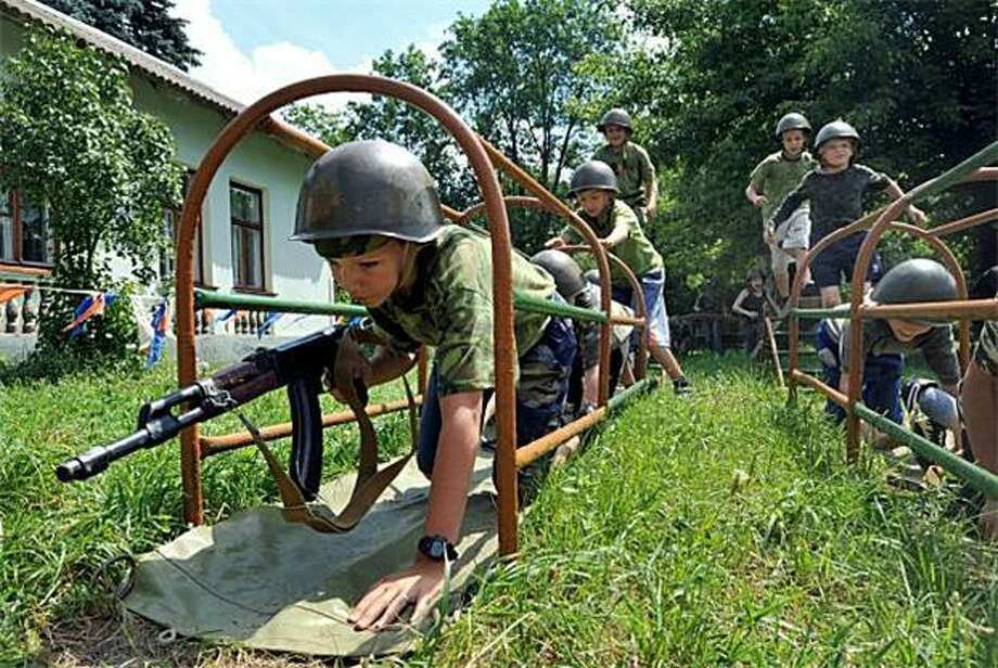 Dear Mom and Dad, today at camp we learned how to take out a bunker: A military-themed summer camp runs Belarusian boys through an obstacle course in the village of Zhodino. The AK-47s are wooden models. Photo: Viktor Drachev, AFP / Getty Images / AFP / Getty Images