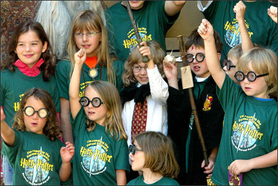 "Young Harry Potter fans demonstrate how they would hold a broomstick at a ""Harry Potter"" party at Cafe Appassionato sponsored by Canadian publisher Raincoast Books and the Boreal Songbird Initiative. The children learned that a recycled-paper edition of ""Harry Potter and the Half-Blood Prince"" -- out at midnight May 16 -- is available in Canada. They e-mailed the book's U.S. publisher, asking that it also print the book on recycled paper. Photo: Meryl Schenker, Seattle Post-Intelligencer / Seattle Post-Intelligencer"