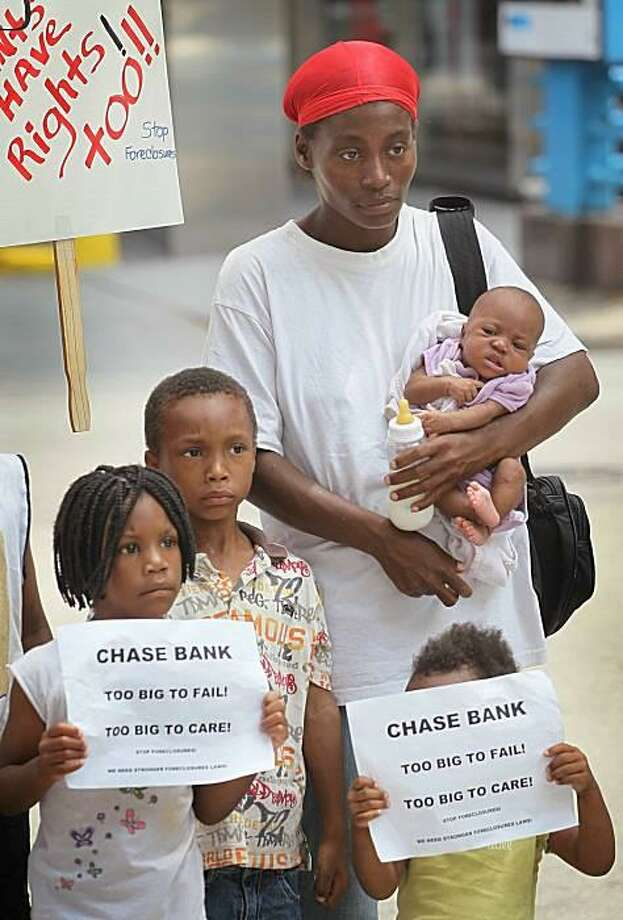 Facing eviction from their apartment building, Crystal Richard and her kids picket JPMorgan Chase in Chicago. The city deemed the building uninhabitable and ordered residents out by Saturday. Residents claim the building was not maintained after the bank took it over following a 2008 foreclosure. Photo: Scott Olson, Getty Images / Getty Images