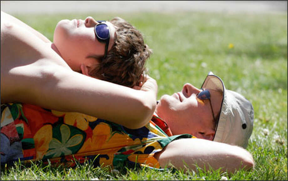 Nick Holt and son Nigel, 11, soak up the sun at the Mediterranean Fantasy Festival at Hiawatha Playground in West Seattle. The festival, in its 18th year, featured two days of bellydancing with dozens of participants. Nigel didn't like the grass, so he used his dad as a cushion instead. Photo: Meryl Schenker, Seattle Post-Intelligencer / Seattle Post-Intelligencer