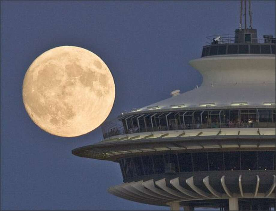 Visitors to the Space Needle enjoy a nearly full mooon as it rises over Seattle. The picture was taken from Queen Anne Hill. Photo: Grant M. Haller, Seattle Post-Intelligencer / Seattle Post-Intelligencer