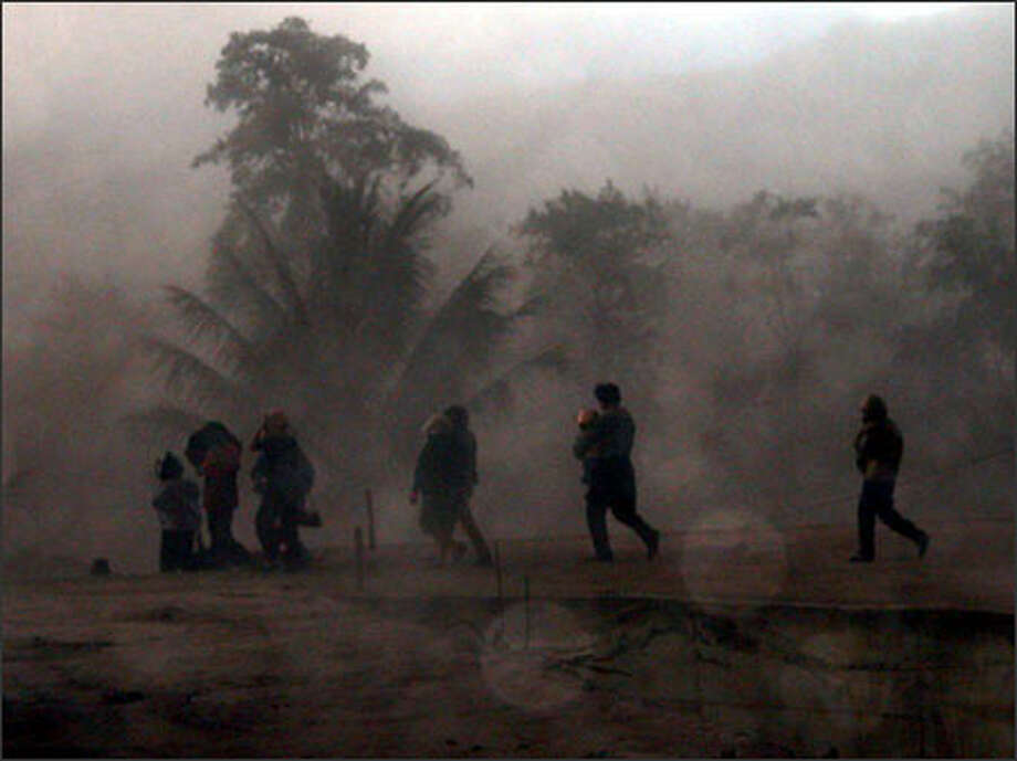 Residents walk in heavy volcanic ashes spewed from the crater of the 5,849-foot Mount Soputan as they flee their homes in North Sulawesi, Friday, July 18, 2003. The volcano erupted Friday in eastern Indonesia, spewing lava and clouds of dust high into the air, officials said. (AP Photo/Dino Gobel) Photo: Seattle Post-Intelligencer / Seattle Post-Intelligencer
