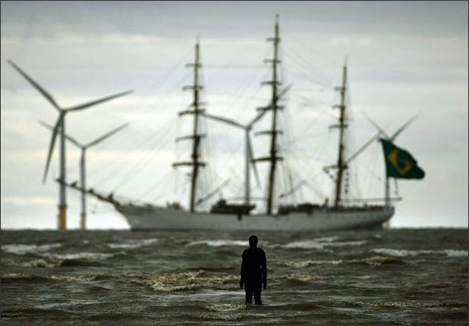 A figure from Antony Gormley's 'Another Place' welcomes one of the Tall Ships to Merseyside as it sails past the Burbo Bank windfarm on the approach to the Port of Liverpool, England. Photo: Getty Images / Getty Images