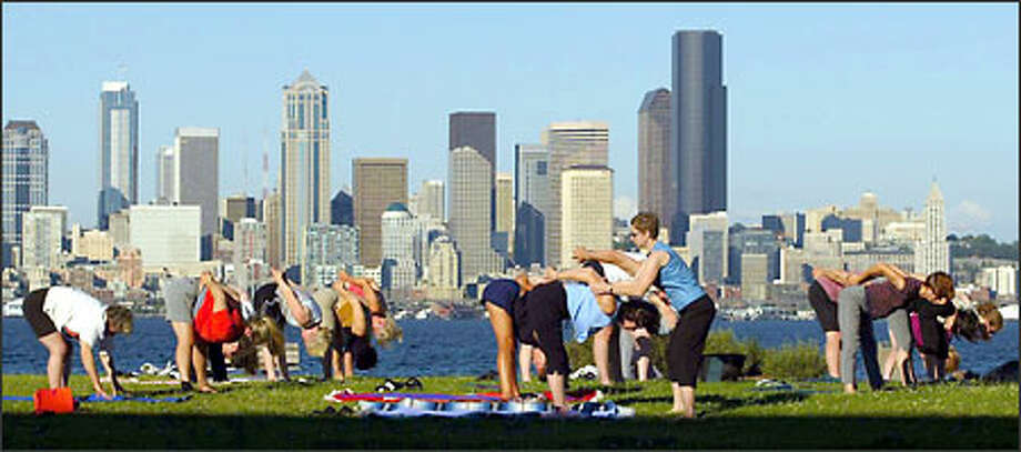 Instructor Tracy Decroce adjusts Kathleen O'Meara's arm during a free yoga class offered by the West Seattle Family YMCA on Wednesdays at 6 p.m. The class meets at Don Armeni Park. Photo: Grant M. Haller, Seattle Post-Intelligencer / Seattle Post-Intelligencer
