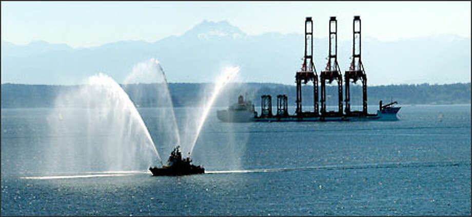 A Seattle fireboat welcome three new, fully assembled 391-foot-high Shanghai China container cranes to Elliott Bay, where they will be installed at Terminal 46. Photo: Grant M. Haller, Seattle Post-Intelligencer / Seattle Post-Intelligencer
