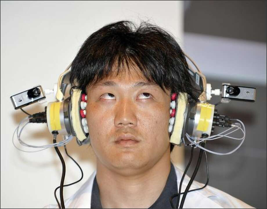 A researcher for Japanese mobile communication giant NTT docomo, wearing electro-oculogram (EOG) sensors, moves his eyes to control a digital music player during a demonstration of their advanced technology at the Wireless Japan Expo in Tokyo. Photo: Getty Images / Getty Images