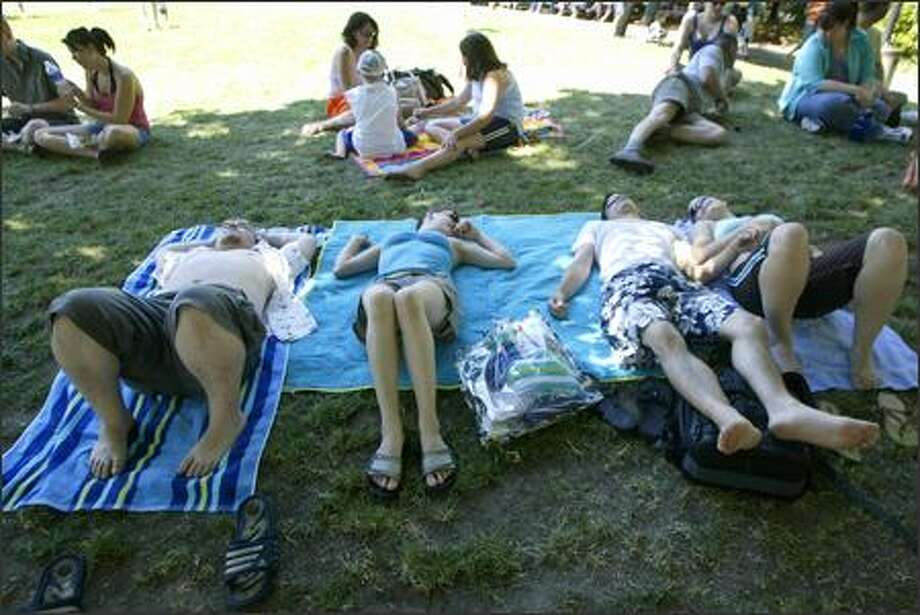 Bellevue residents, from left, Kevan Kopra, Krista Henderson, Joe Anderson and Joey Hammer find a shady spot beneath a tree to keep cool while enjoying the outdoors music at the Bite of Seattle, held at the Seattle Center.  The temperature hit 95 degrees on Sunday, still short of the record of 99 degrees set in 1991. Photo: Jim Bryant, Seattle Post-Intelligencer / Seattle Post-Intelligencer