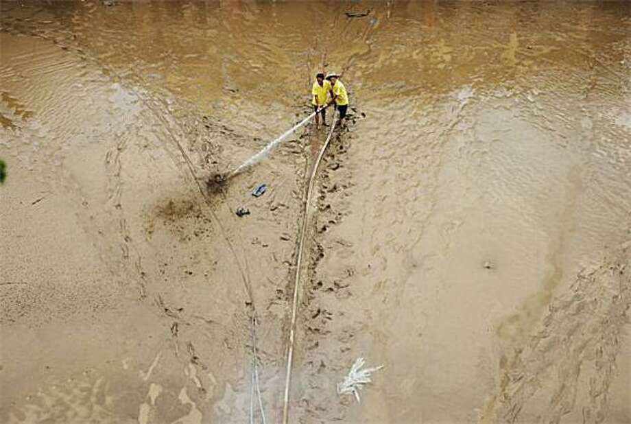Muddy mess:Chinese workers try to hose flood mud off a street after the Jialing River overflowed its banks in Chongqing. China, already reeling from a series of deadly floods, braced for a potential new deluge on the Yangtze downstream from the huge Three Gorges Dam. Photo: Str, AFP / Getty Images / AFP / Getty Images