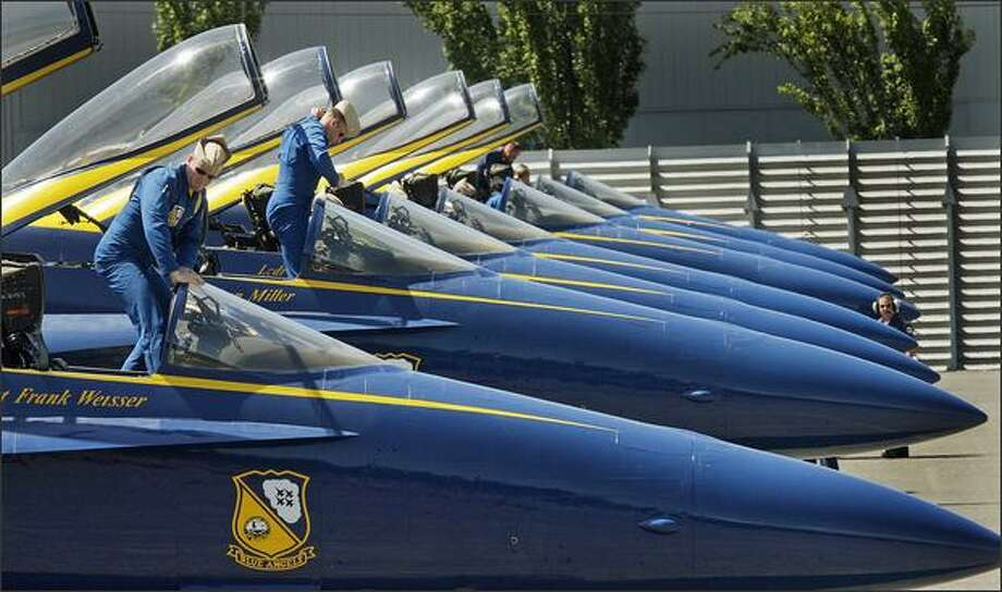 The Blue Angels pilots Lt. Frank Weisser, left, and Maj. Nathan Miller disembark after landing their F/A-18 Hornets at Boeing Field in Seattle on Monday. The U. S. Navy's Flight Demonstration Squadron will perform at Seafair later in the week. Photo: Dan DeLong, Seattle Post-Intelligencer / Seattle Post-Intelligencer