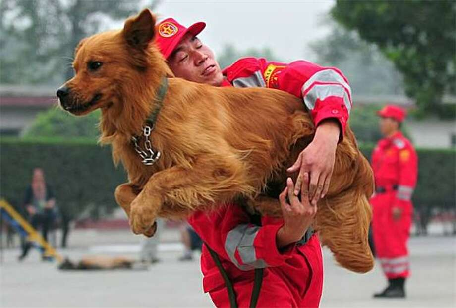 "The entire budget was spent on hot-pink jumpsuits:One day the Engineering Regiment of the People's Liberation Army in Beijing will be able to afford actual hoops for their search-and-rescue dogs to leap through. Until then, they'll keep making ""O's"" with their arms. Photo: Frederic J. Brown, AFP / Getty Images / AFP / Getty Images"
