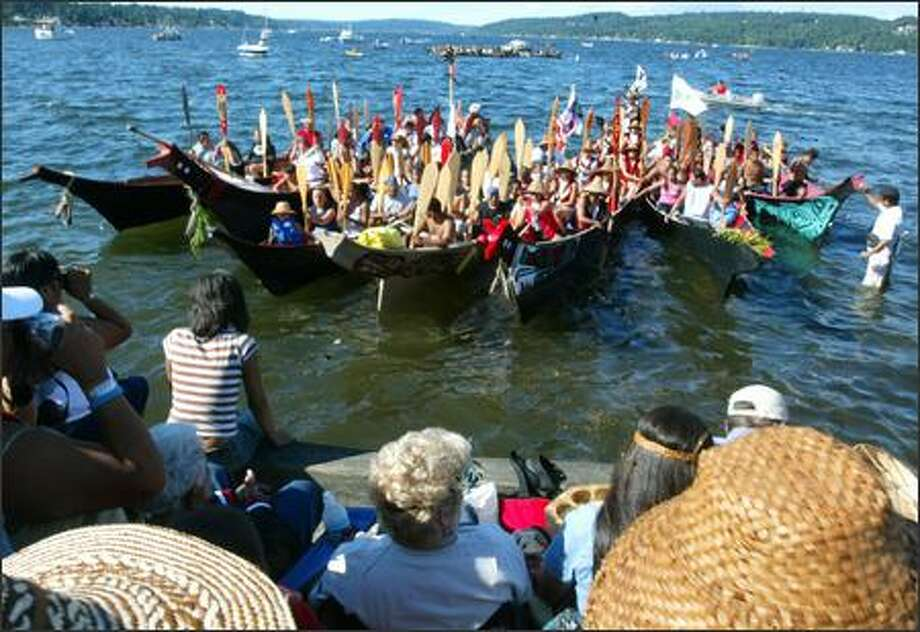 Members of the Salish tribes ask members of the Muckleshoot Tribe for permission to come ashore Monday at Sand Point. More than 50 canoes arrived Monday in Seattle, after traveling across Puget Sound, through the Ballard Locks and into Lake Washington, for a five-day celebration and cultural exchange. In the distance, a group from the south Puget Sound area awaits its turn to land. Photo: Grant M. Haller, Seattle Post-Intelligencer / Seattle Post-Intelligencer
