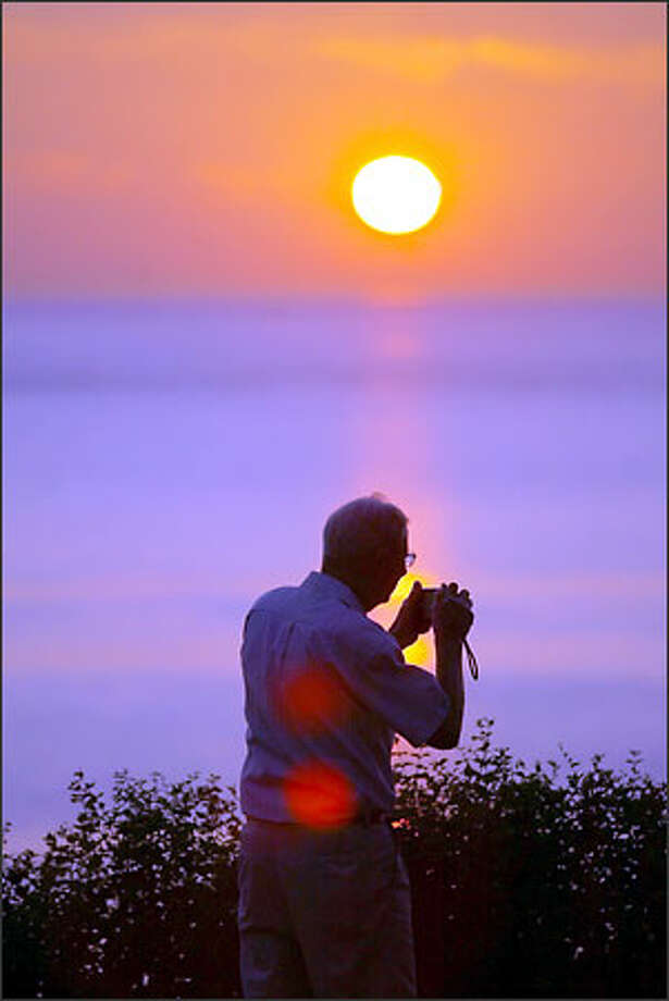 As the sun sinks into the ocean off the coast of Lummi Island, Irving Lund of Karlby, Denmark, who is in the area visiting his son, who lives in Olympia, adjusts the settings on his camera so he can capture the moment. Photo: Scott Eklund, Seattle Post-Intelligencer / Seattle Post-Intelligencer