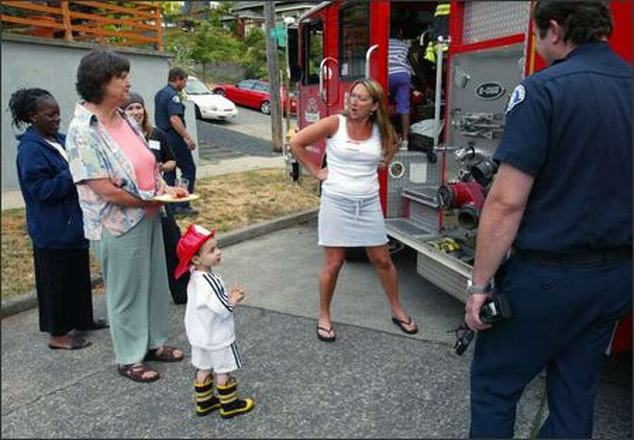 "Susan Clark, second from right, tries to talk Sandor Weiss, age 3 1/2, into climbing up into the cab of Seattle Fire Department Engine 20 during a ""National Night Out"" block party on the 2800 block of 11th Avenue West on Queen Anne Hill.  Sandor, who brought along his own firefighter's hat and boots, decided to get some food instead.    Neighbors at this party also paused to remember Pamela Waechter, who was shot to death last Friday at the Jewish Federation of Greater Seattle, and collected money to plant a tree in a traffic circle in her memory. Photo: Grant M. Haller, Seattle Post-Intelligencer / Seattle Post-Intelligencer"