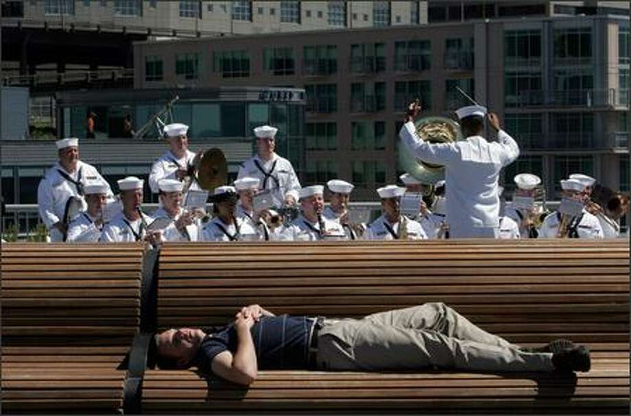 Jake Zastrow probably wasn't expecting accompaniment by the U.S. Navy Band while resting Wednesday at Pier 66. Photo: Meryl Schenker, Seattle Post-Intelligencer / Seattle Post-Intelligencer