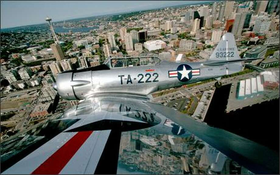 Stunt pilot Bill Leff flies over Seattle in his 1940s-era North American T-6G trainer Thursday in preparation for part of the KeyBank Air Show at Seafair. On Saturday night, Leff will perform Seafair's first nighttime air show; it'll include fireworks, pyrotechnic effects and a light show. This photo was made using a camera on the wingtip, triggered by remote control from the cockpit by the photographer (who is ducking in the back seat). Photo: Joshua Trujillo, Seattlepi.com / seattlepi.com
