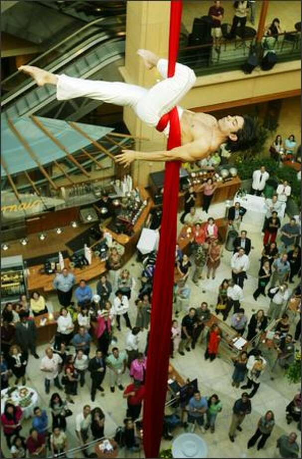 Aerial artist Sam Alvarez dangles 60 feet above a crowd in the atrium at Pacific Place in downtown Seattle. Alvarez is giving four shows a week in August to promote Seattle's Teatro Zinzanni. Photo: Scott Eklund, Seattle Post-Intelligencer / Seattle Post-Intelligencer