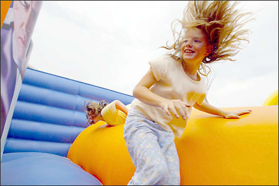 Erin Worley, 9, enjoys some hair-raising fun as she negotiates her way with a fellow camper through an inflatable obstacle course at a YMCA day camp jamboree. Photo: Meryl Schenker, Seattle Post-Intelligencer / Seattle Post-Intelligencer