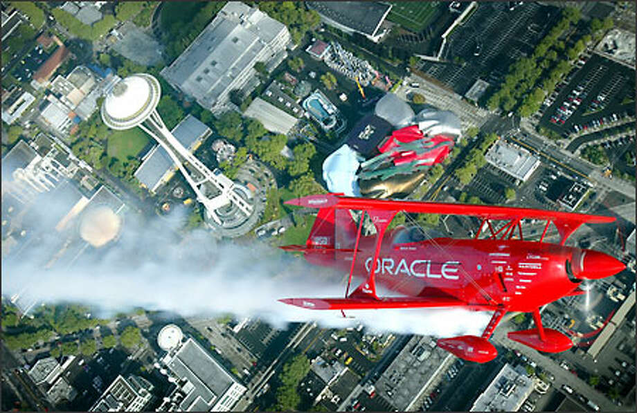 "The Oracle Challenger stunt plane makes a pass over the Space Needle and Experience Music Project during a tour of the area. Pilot Sean Tucker, named by the Smithsonian Air and Space Museum as one of the 25 ""Living Legends of Flight,"" was preparing for the KeyBank Air Show at Seafair. Photo: Joshua Trujillo, Seattlepi.com / seattlepi.com"