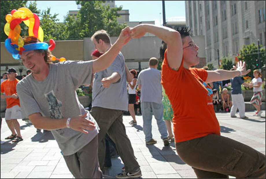 David Poole, left, of Tacoma dances with Mallorhee of Olympia at the sixth annual Lindy Hop Swing Dance Exchange Sunday afternoon at the square across from Westlake Center in downtown Seattle. An exchange, in swing dance terms, is a chance for the dancers of one city to invite other dancers from across the country -- or sometimes across the world -- to visit and dance nightly into the early hours of the morning. The event, organized by the local Savoy Swing Club, featured three days of dancing to live bands and local DJs at dance venues such as the Century Ballroom and the Washington Dance Club. Photo: Niki Desautels, Seattle Post-Intelligencer / SEATTLE POST-INTELLIGENCER
