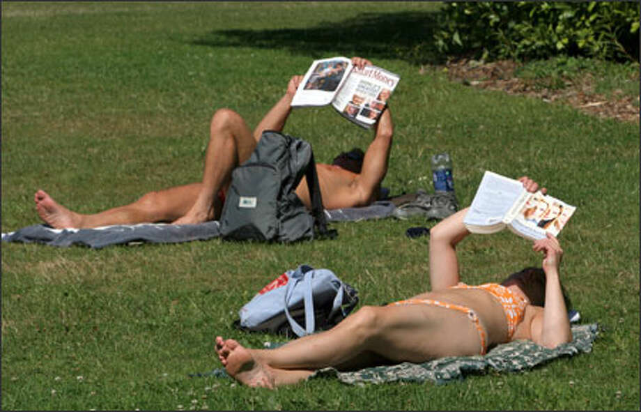 Though skin cancer runs in her family, Robin Posey, right, sunbathing Tuesday at Volunteer Park, says she doesn't use sunscreen because the sun is too tempting. She limits her time to one hour, however. Photo: Meryl Schenker, Seattle Post-Intelligencer / Seattle Post-Intelligencer