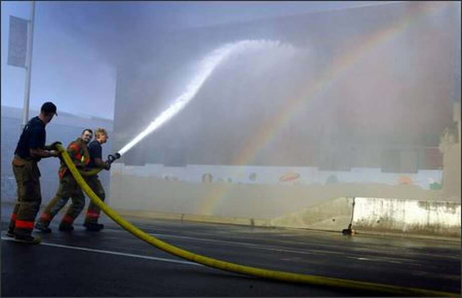 Firefighters work to bring a warehouse fire under control near Safeco Field. Fire quickly engulfed a two-story warehouse south of downtown, and spread to a second building early Wednesday morning. The two-alarm fire began around 5:30 a.m., and within a half hour the roof of the warehouse had collapsed, forcing firefighters to battle the blaze from the exterior. (Seattle Post-Intelligencer, Joshua Trujillo Photo: Joshua Trujillo, Seattlepi.com / seattlepi.com