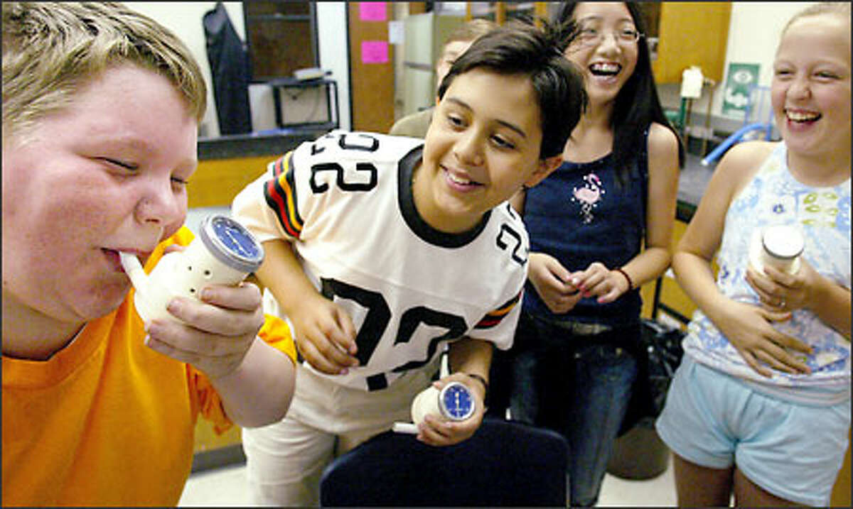 As part of a Summer Science Camp at Bellevue Community College, students were given the opportunity to test their lung capacity. Shawn Bongard, left, went first, much to the amusement of fellow students, from left, Alex Matos, Tiffany Huang and Rachel Best.