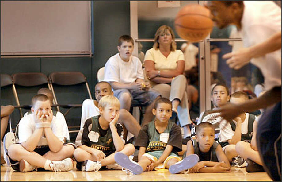 Young campers at the Seattle Sonics and Seattle Storm basketball camp watch intently as they get instruction on basketball techniques. The camp runs through Wednesday from 9 a.m. to 4 p.m. at the Furtado Center in the Seattle Center. Photo: Scott Eklund, Seattle Post-Intelligencer / Seattle Post-Intelligencer