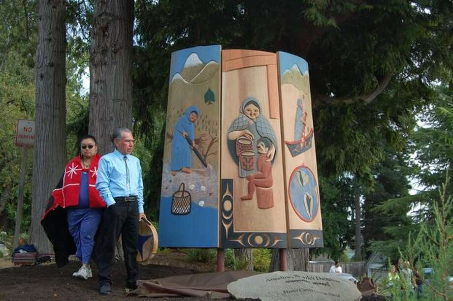 A carving depicting the life of Princess Angeline, daughter of Chief Seattle, was unveiled Saturday in a small neighborhood park in Suquamish during the Suquamish Tribe's 100th annual Chief Seattle Days celebration. Master Carver George David from Vancouver Island, with drum, explained that the first panel he created represents Angeline digging clams as a child, and the others show her as she aged. Photo: Eric Nalder, Hearst Newspapers / Hearst Newspapers