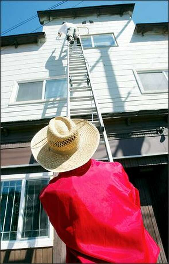 Boon Souknirandone steadies the ladder Wednesday while his painting-contractor son, Tony, hits the high spots on a house on the corner of Rainier Avenue South and South Holly Street. Boon is a retired roofer who immigrated to Seattle from Laos. All the recent sunny weather has been perfect for putting fresh coats on area houses. Photo: Paul Joseph Brown, Seattle Post-Intelligencer / Seattle Post-Intelligencer