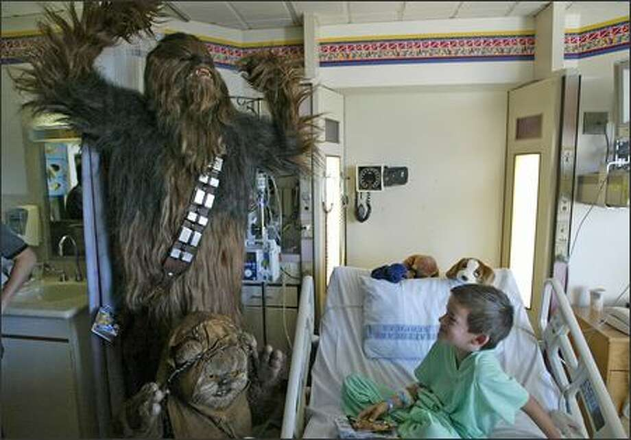 "The news that Matthew Proctor's favorite ""Star Wars"" character is the Ewok Wicket elicits a less-than-happy response from Chewbacca, Han Solo's faithful Wookiee co-pilot, during a visit Monday with patients at Swedish Medical Center. Matthew, a 7-year-old from Fall City, has been stuck in the hospital for 10 days with an eye infection. Darth Vader also greeted kids at the kickoff to a 12-day tour of the United States to promote upcoming movie-related releases. Photo: Gilbert W. Arias, Seattle Post-Intelligencer / Seattle Post-Intelligencer"