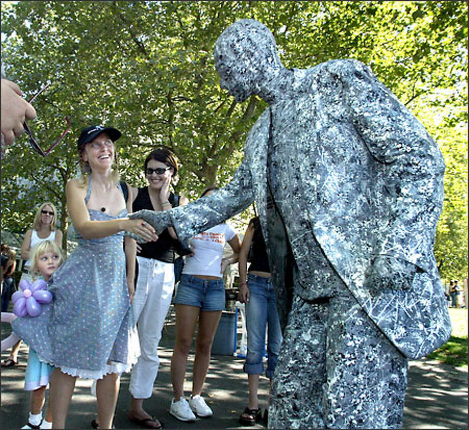 "Allison Hill, visiting from Austin, Texas, shakes hands with ""living statue"" Jesse Ferguson at Bumbershoot while her daughter, Sita Lynn Hill, 4, hides behind her skirt. Photo: Karen Ducey, Seattle Post-Intelligencer / Seattle Post-Intelligencer"