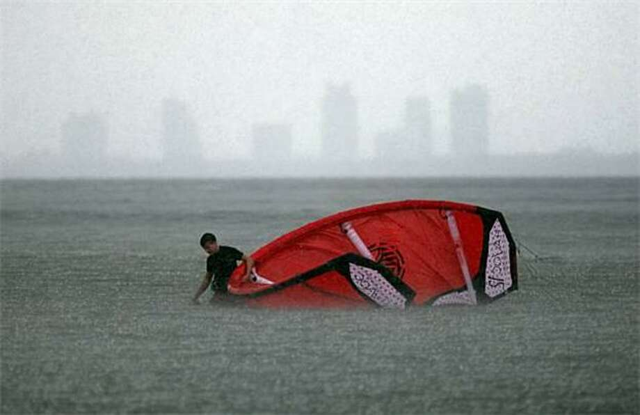 The kite walker:A kite surfer gives up on the surfing part and walks his kite to shore in a downpour spawned by Hurricane Earl in Miami. Photo: Joe Raedle, Getty Images / Getty Images