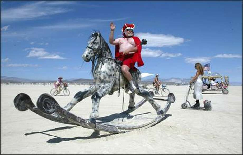"Mike Hall, aka ""King Mickey,"" a 54-year-old from Dutch Flats, Calif., waves from atop a giant rocking horse on the playa at Burning Man, which is expected to draw 35,000 participants this year to  Black Rock, Nev. Photo: Gilbert W. Arias, Seattle Post-Intelligencer / Seattle Post-Intelligencer"