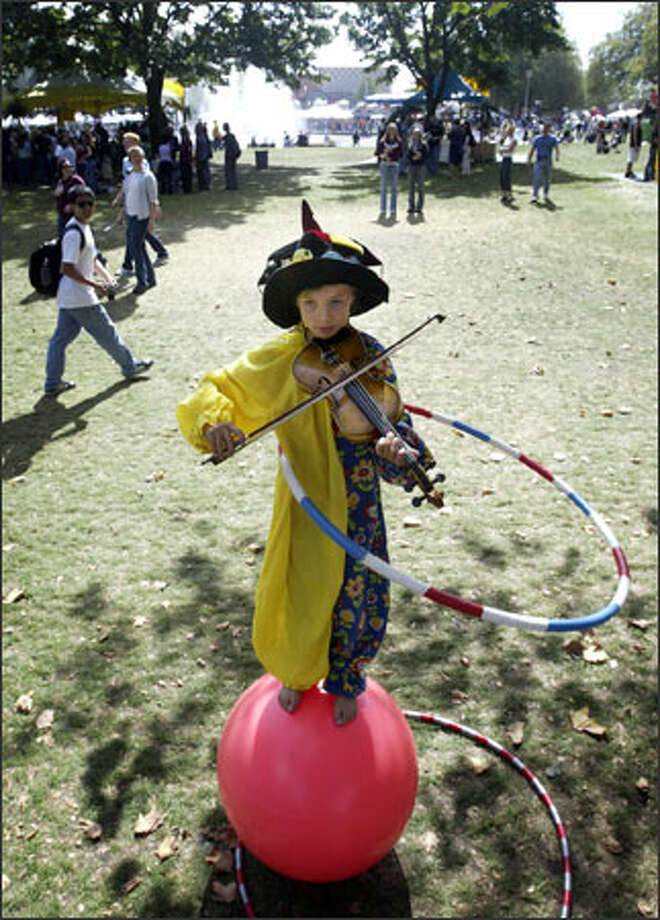 Balancing on a rubber ball and twirling a hula hoop, 9-year-old Una Bennett plays the violin at Bumbershoot. She and her juggling brother, Ezra Weill, 12, can earn $200 to $300 a day. Photo: Dan DeLong, Seattle Post-Intelligencer / Seattle Post-Intelligencer