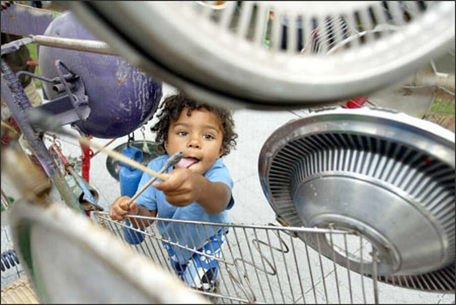 "Habib Ceesay, 2, of Seattle pounds out a rhythm on hubcaps that are part of Ben Smith's interactive musical sculpture ""Junk Chime Jamming"" at Bumbershoot. Photo: Meryl Schenker, Seattle Post-Intelligencer / Seattle Post-Intelligencer"