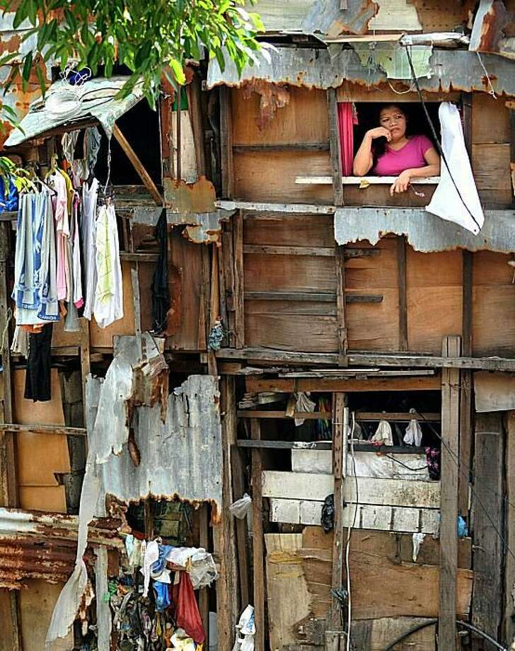 The shanty life:A woman watches the street from a window of her makeshift apartment in a slum in the heart of Manila. Despite a robust economy, about half of the Philippine population considers themselves poor, according to a new study by the research group Social Weather Stations. Photo: Jay Directo, AFP / Getty Images / AFP / Getty Images