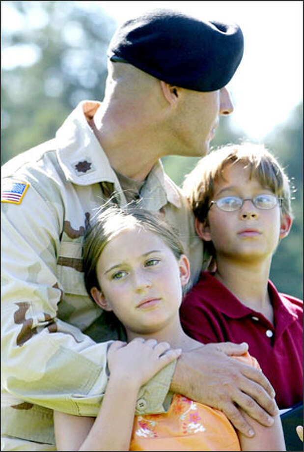 Maj. Nick Mullen, operations officer for the 321st Infantry Division, hugs his children, Haley, 10, and Alex, 11, after a deployment ceremony for the 1st Stryker Brigade at Fort Lewis. Mullen is headed for Iraq. Photo: Meryl Schenker, Seattle Post-Intelligencer / Seattle Post-Intelligencer
