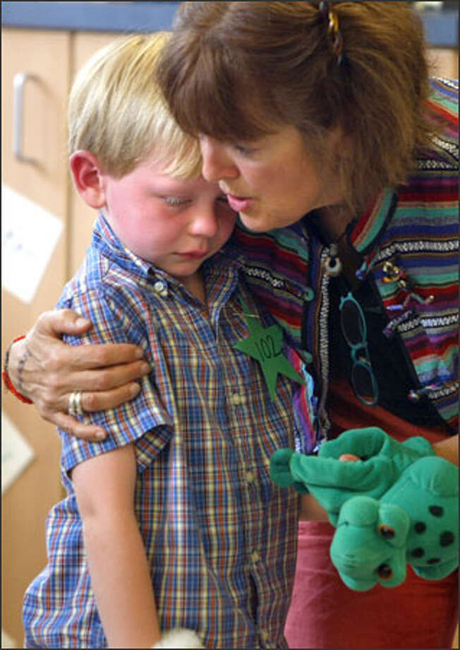 Veteran teacher Kathleen Baker comforts Carter Petro on his first day of kindergarten Wednesday at Greenwood Elementary School. Photo: Karen Ducey, Seattle Post-Intelligencer / Seattle Post-Intelligencer
