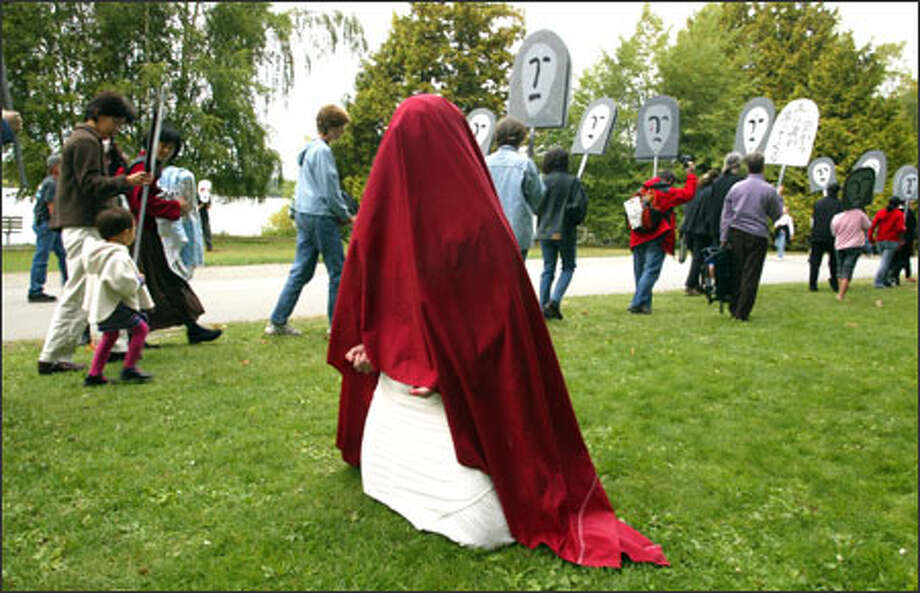 "Delilah Flynn is draped in red shroud at Green Lake Park on Sunday. She and other performers used masks, music, poetry and dance to enact ""Sleeping Apocalypse: 9/11."" Photo: Gilbert W. Arias, Seattle Post-Intelligencer / SEATTLE POST-INTELLIGENCER"