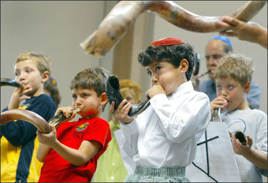 Zachary Battray, 9, left, Robert Singer, 7, Noah Santiago, 7, and Alon Patashnik, 9, put their all into it as they blow shofars at Temple Beth Am in Seattle during a rehearsal for a musical piece to be played on Rosh Hashanah. The Jewish new year starts Wednesday evening, and the sound of the shofar, or ram's horn, is supposed to awaken listeners to re-examine their lives in order to better themselves in the coming year. Photo: Meryl Schenker, Seattle Post-Intelligencer / Seattle Post-Intelligencer