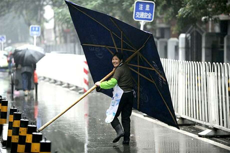 One gust of wind and she'll be airborne:A woman carries an giant umbrella during heavy rain in Beijing. Photo: Peter Parks, AFP / Getty Images / AFP / Getty Images