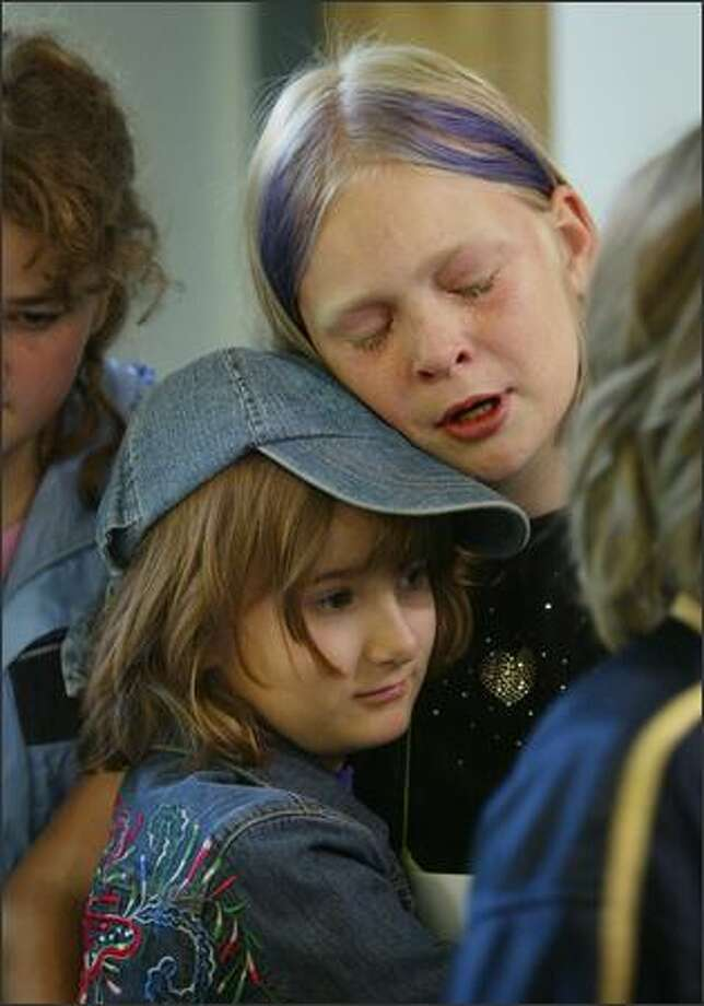 Teary-eyed over the news that Seattle's Alternative School No. 1 has been targeted for closure, Becca Mussman, a fifth-grader, hugs third-grader Ellie Preston. Photo: Dan DeLong, Seattle Post-Intelligencer / Seattle Post-Intelligencer
