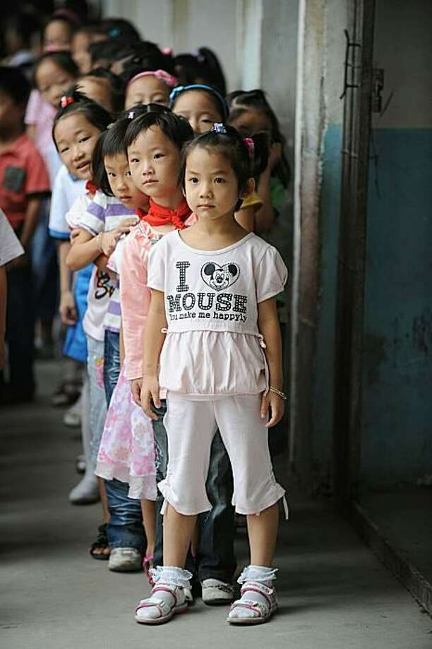 "Probably not purchased at the Disney Store:At a school in Hefei, a Chinese girl wears a shirt that reads: ""I (heart) Mouse/You make me happyly."" Photo: Str, AFP / Getty Images / AFP / Getty Images"
