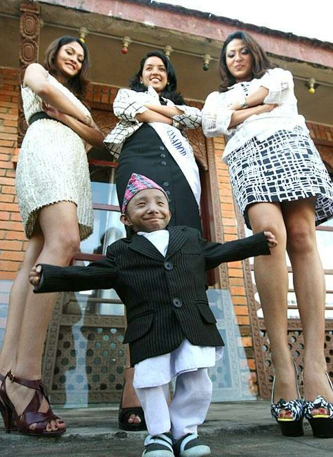 Ladies man:Being the smallest teenager in the world has its advantages, not the least of which is getting to hang out with Miss Nepal, and the first and second runner-ups in Katmandu. Khagendra Thapa Magar, 22 inches tall and weighing less than 10 pounds, is waiting to be declared the world's smallest man on Oct. 14, when he turns 18. Photo: Prakash Mathema, AFP / Getty Images / AFP / Getty Images
