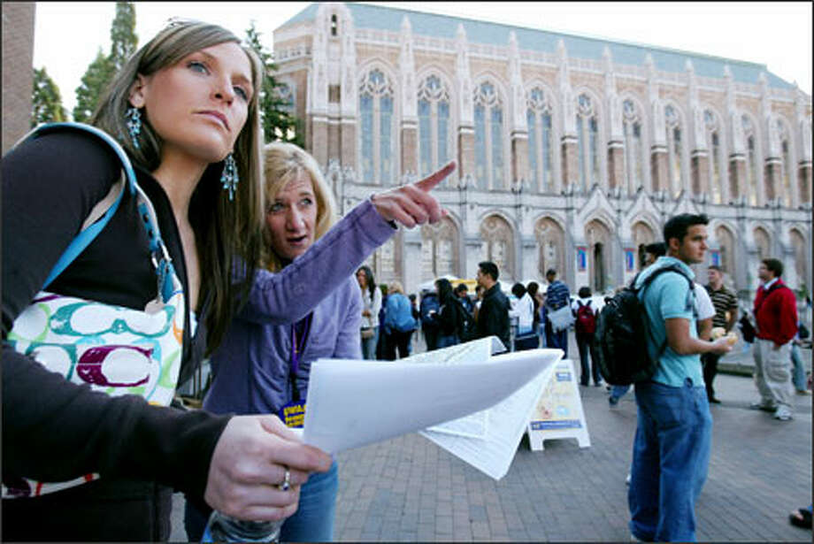 On Wednesday, the first day of classes at the University of Washington, Janine Johnson helps Cassie Cleveland find her way to class. Johnson was volunteering with an alumni group helping new students navigate the campus and handing out free coffee, bagels and donuts. Photo: Paul Joseph Brown, Seattle Post-Intelligencer / Seattle Post-Intelligencer